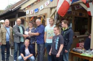 Jean-Louis Jacquet vom Rumillyzelt auf dem Michelstädter Bienenmarkt übergibt Michael Reiß vom Beruflichen Schulzentrum Odenwald ein Geldkuvert.